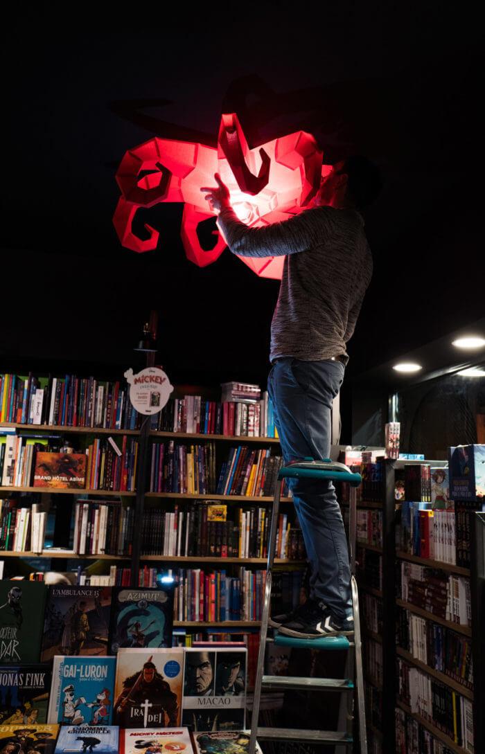 Librairie Octopus pose d'un luminaire dans la librairie par Armand pour atelier-atelier