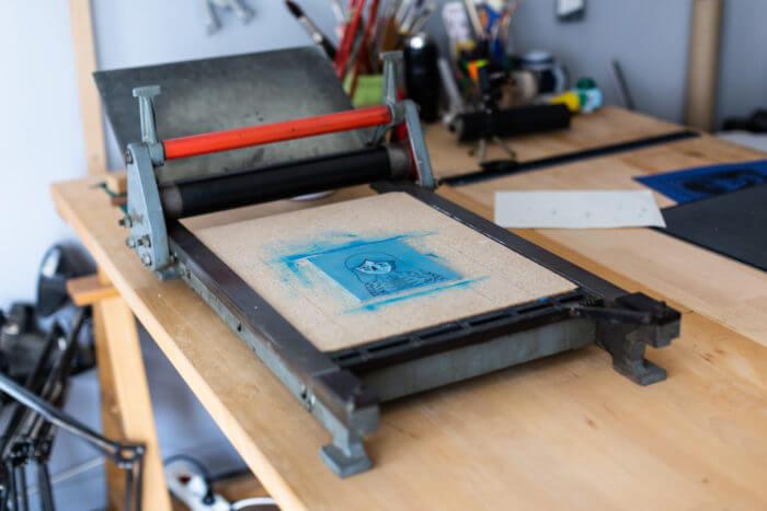 Presse typographique à épreuve JUD installée sur le plan de travail à l'atelier à Remiremont Vosges